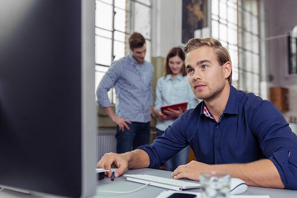 Busy office with a hardworking young man sitting at his desktop computer in the foreground with his colleagues have a discussion over paperwork in the background